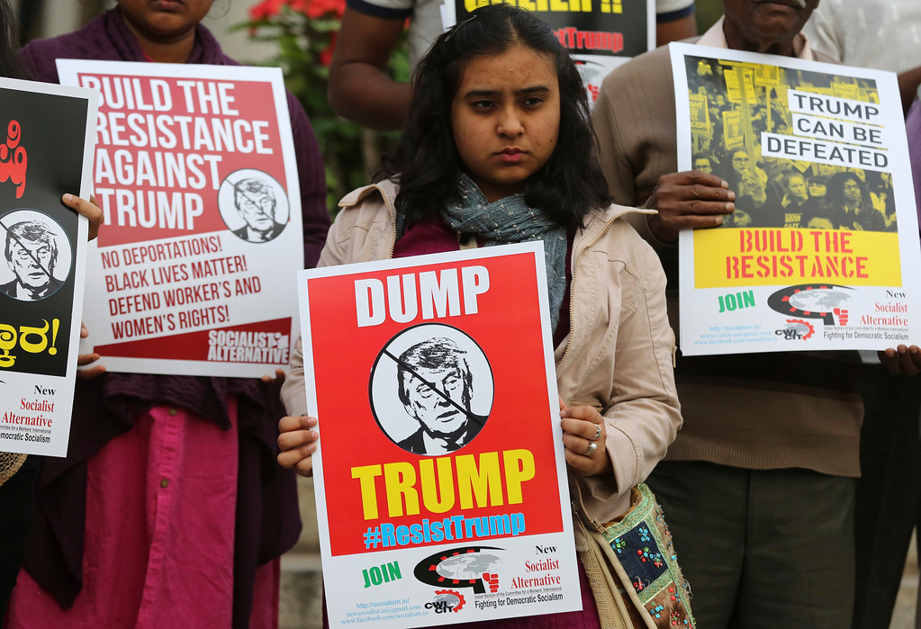 . A young Indian woman holds a placard as she listens to a speaker during a protest demonstration against U.S. President Donald Trump in Bangalore, India, Saturday, Jan. 21, 2017. The protest is part of a worldwide day of actions following the inauguration of U.S President Donald Trump. (AP Photo/Aijaz Rahi)