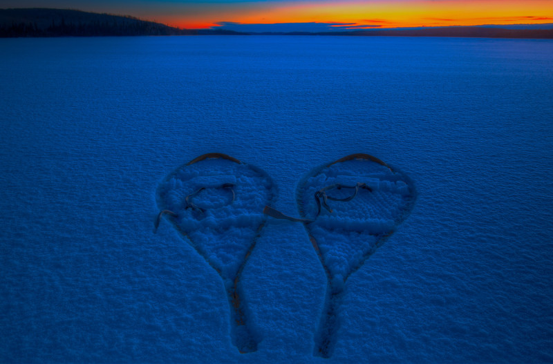 Snowshoes in the snow at sunrise