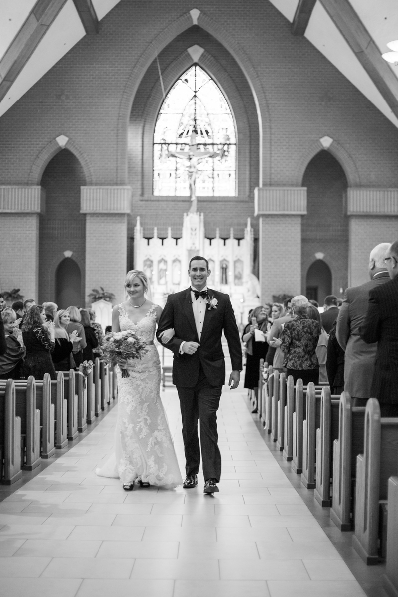 Happy bride and groom walk down the aisle after their Catholic wedding ceremony and before the Bluemont Vineyard wedding reception. Photos by the best Northern Virginia wedding photographer Jalapeno Photography. The Catholic wedding ceremony was at St. Theresa Catholic Church in Ashburn, VA.
