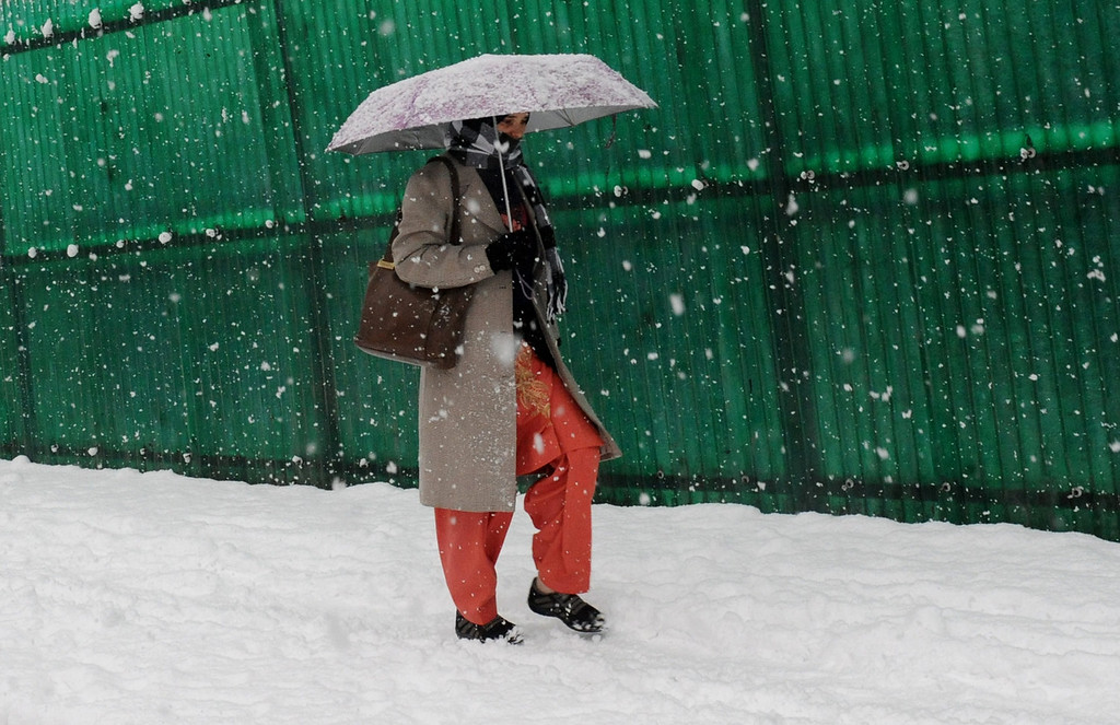 . A Kashmiri pedestrian walks during a snowfall in Srinagar on December 31, 2013. A cold wave further tightened its grip in Jammu and Kashmir with most places in the state recording sub-zero temperatures. ROUF BHAT/AFP/Getty Images