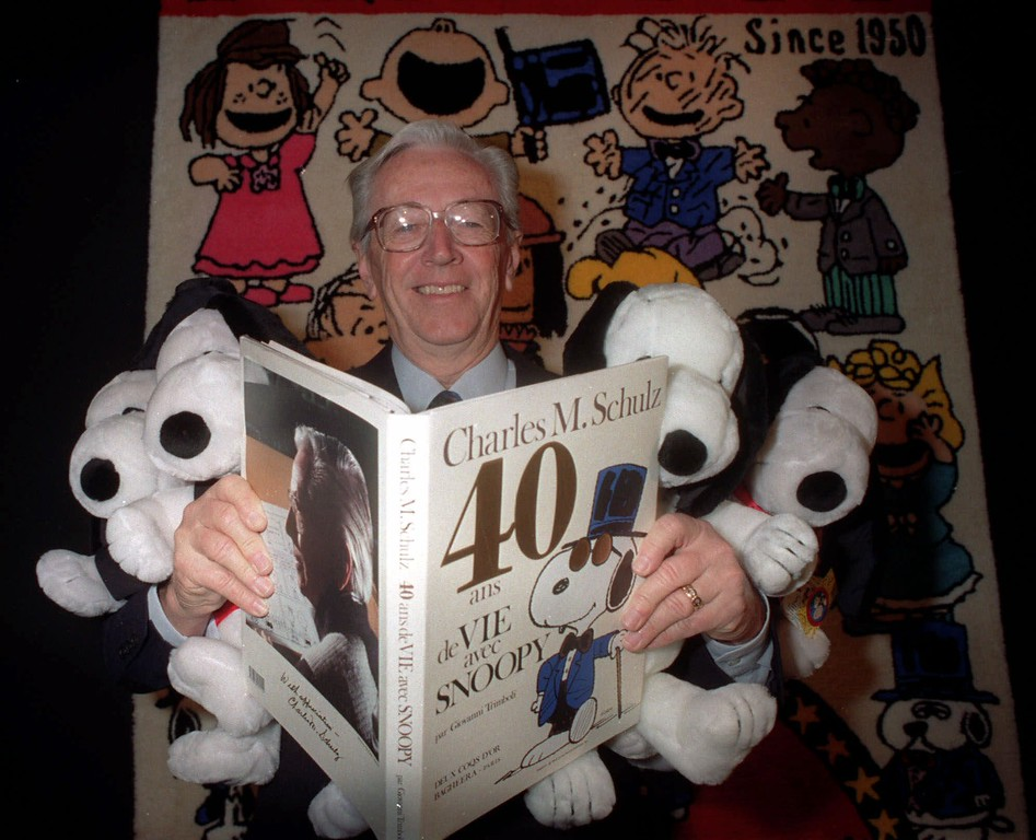 . Snoopy\'s creator Charles Schulz, smiles while he carry his book, 40 years of life with Snoopy, and four Snoopy toys in Paris on Tuesday Jan. 23, 1990. Schulz, 77, who has written, drawn, colored and lettered every ``Peanuts\'\' strip, announced Tuesday that his last new daily installment will appear Jan. 3 and his last new Sunday strip will be published Feb. 13. Schulz was diagnosed with colon cancer last month. ( AP Photo / Michel Lipchitz)