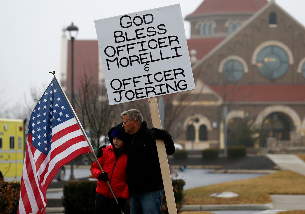 . Bob Votruba, right, and his nephew Mason Miller, 13, stand outside of St. Paul the Apostle Catholic Church in in Westerville, Ohio, before the start of funeral services for Westerville police officers Anthony Morelli and Eric Joering at the church Friday, Feb. 16, 2018.  The two veteran officers were shot after entering a residence early Saturday afternoon.  (AP Photo/Paul Vernon)
