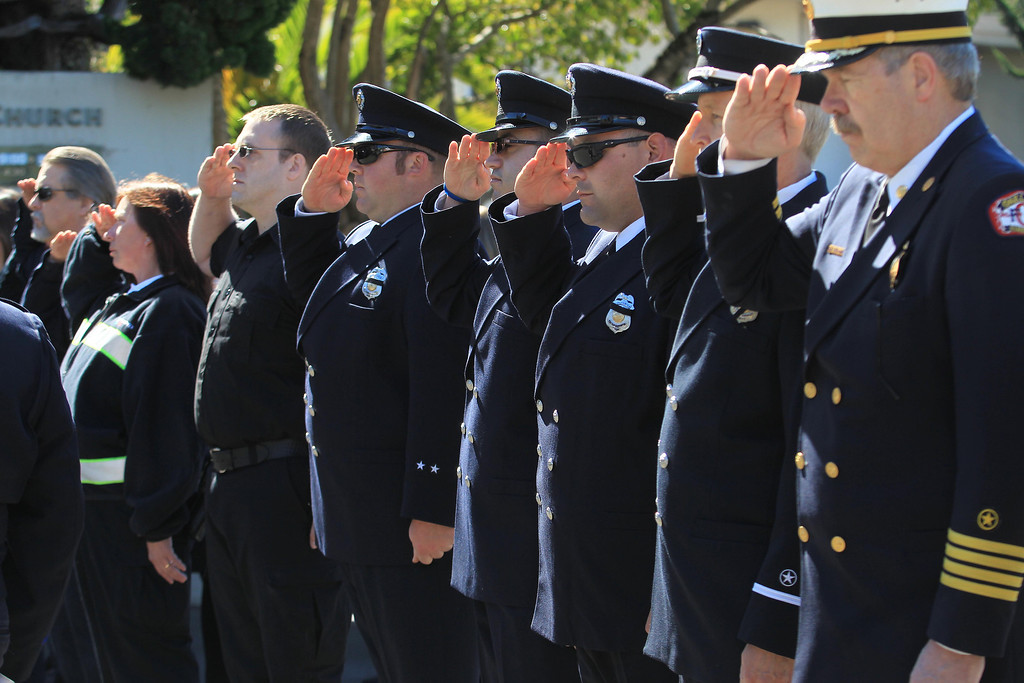 . Oakland firefighters salute during funeral services for Santa Clara paramedic Quinn Boyer, 34, of Dublin, at St. Theresa Catholic Church in Oakland, Calif., on Tuesday, April 16, 2013.  (Jane Tyska/Staff)
