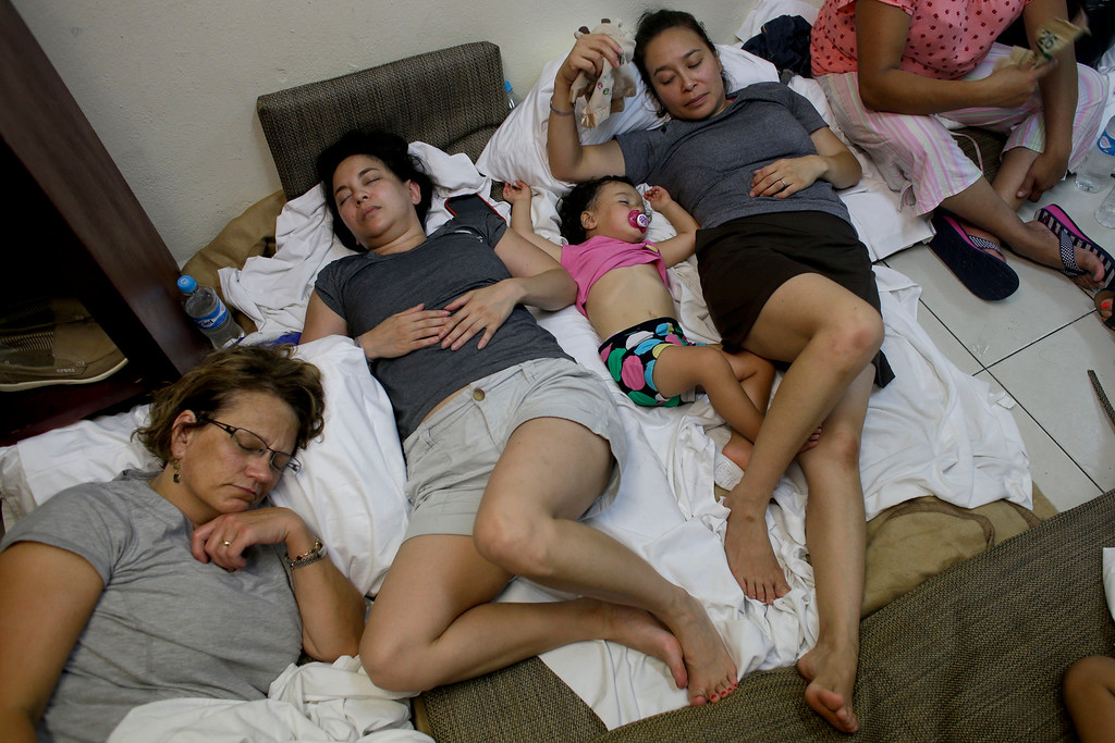 . A Mexican family with their 2-year old toddler rests inside a room in the service area of a resort  after the designated area for shelter was destroyed by winds in Los Cabos, Mexico, Monday, Sept. 15, 2014. Hurricane Odile raked the Baja California Peninsula with strong winds and heavy rains early Monday as locals and tourists in the resort area of Los Cabos began to emerge from shelters and assess the damage. (AP Photo/Victor R. Caivano)