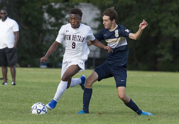 Newington boys soccer defeated New Britain 3-1 on Tuesday afternoon at Newington High School. New Britain's Shevon Traille (9) and Newington's Jason Welch (8). Wesley Bunnell | Staff