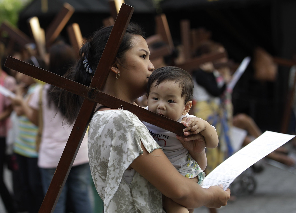 . A Filipino child bites a wooden cross as devotees practice different religious rites during the Holy Week at the Philippine Center of Saint Pio of Pietrelcina on Thursday, March 28, 2013 in suburban Quezon city, east of Manila, Philippines.(AP Photo/Aaron Favila)