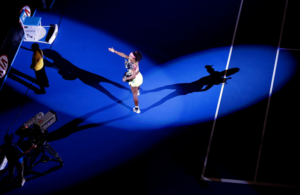 . Serena Williams of the U.S., holding the trophy, parades on Rod Laver Arena,  after defeating Maria Sharapova of Russia in their women\'s singles final at the Australian Open tennis championship in Melbourne, Australia, Saturday, Jan. 31, 2015. (AP Photo/Lee Jin-man)