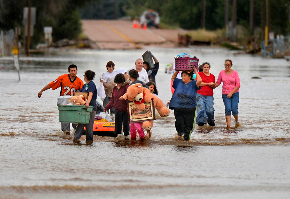 Description of . The floods that hit Colorado this September we truly devastating.  This photo was made within moments of arriving in Evans as residents brought out their belongings. To me this photo had the look and feel of some of the images we saw during hurricane Katrina.  EVANS, CO - SEPTEMBER 16: Residents in Evans carry out belongings from their flooded homes, September 16, 2013. Massive flooding continues to hit Colorado. (Photo By RJ Sangosti/The Denver Post)