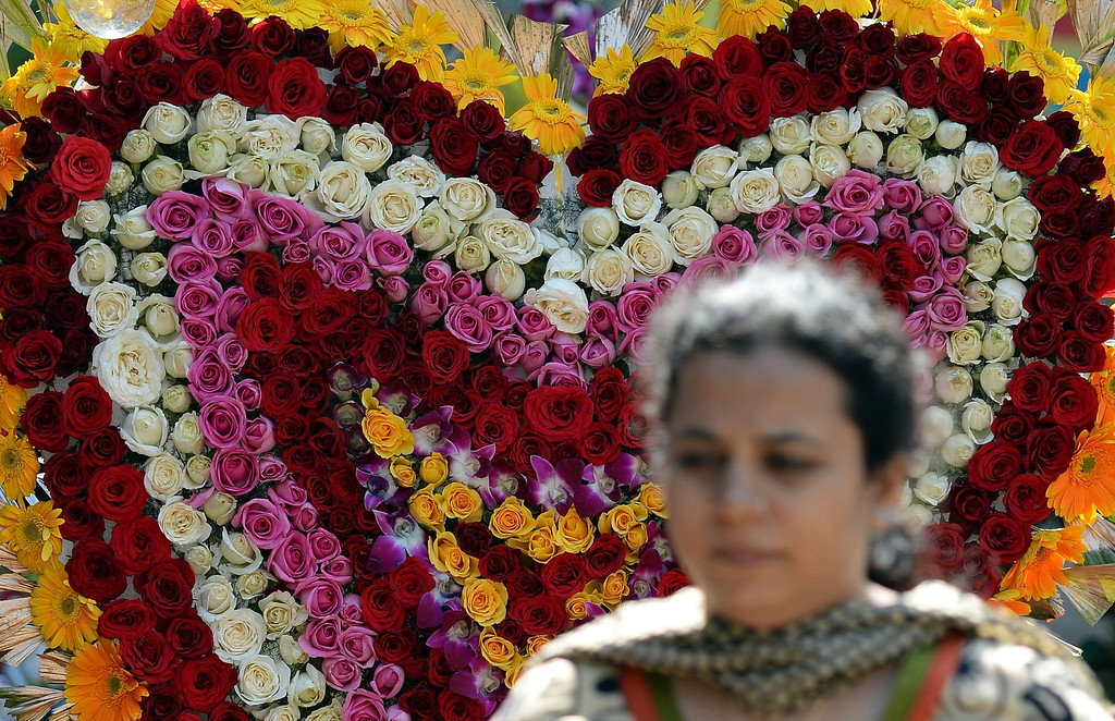 . A pedestrian walks past a heart-shaped flower arrangement made with roses on display at a florist on Valentine\'s Day in Mumbai on February 14, 2014. Valentine\'s Day is celebrated with mixed emotions in India as some right-wing hindu groups view the holiday as a cultural invasion on the Hindu way of life. February 14 also falls on the the death anniversary of three of India\'s most revered freedom icons Bhagat Singh, Sukhdev, and Rajguru, who were executed in 1931. AFP PHOTO/INDRANIL MUKHERJEE/AFP/Getty Images