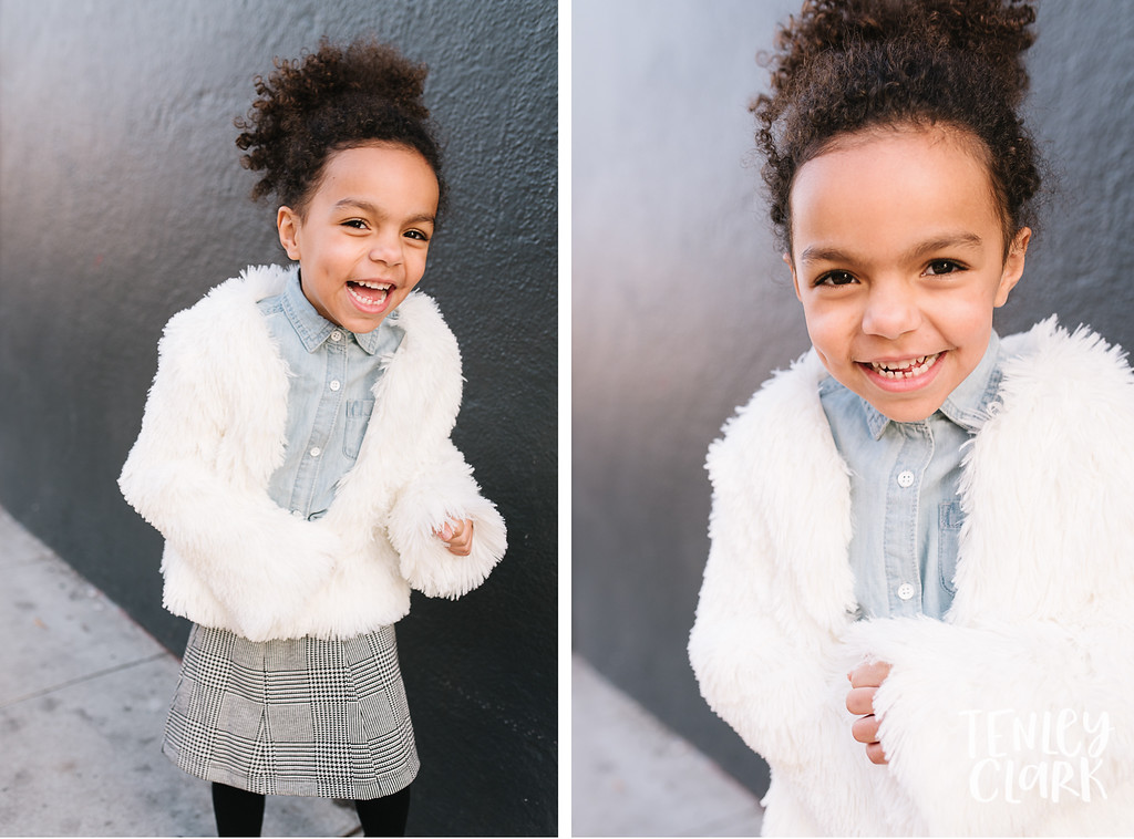 Little girl in fur coat in front of dark gray wall in San Jose by Tenley Clark Photography.