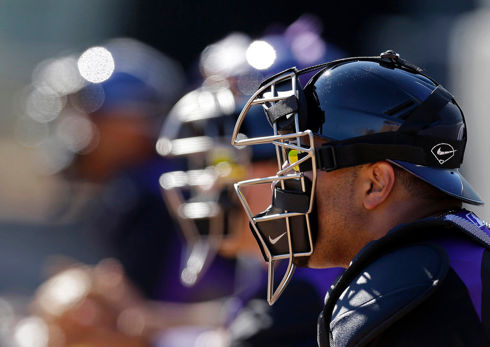 . Colorado Rockies\' Yorvit Torrealba, right, along with other catchers wait for the pitchers during a spring training baseball workout Tuesday, Feb. 12, 2013, in Scottsdale, Ariz. (AP Photo/Darron Cummings)