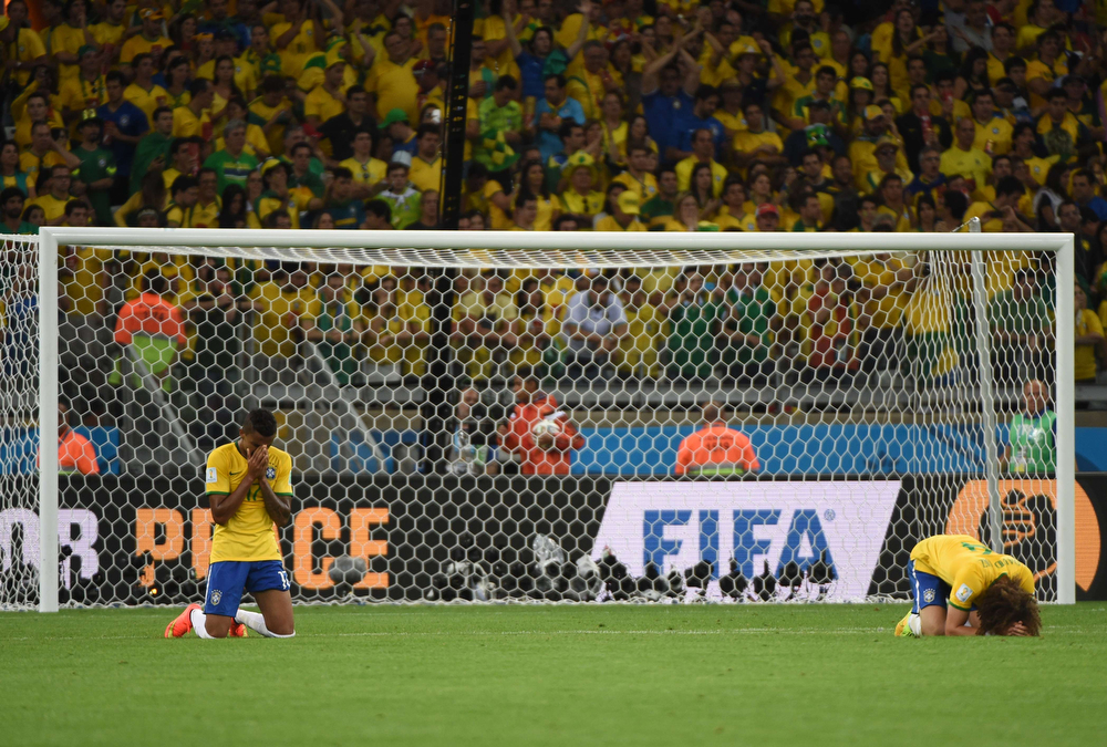 Description of . Brazil's defender David Luiz (R) and Brazil's midfielder Luiz Gustavo react after defeat in the semi-final football match between Brazil and Germany at The Mineirao Stadium in Belo Horizonte on July 8, 2014, during the 2014 FIFA World Cup . (PEDRO UGARTE/AFP/Getty Images)