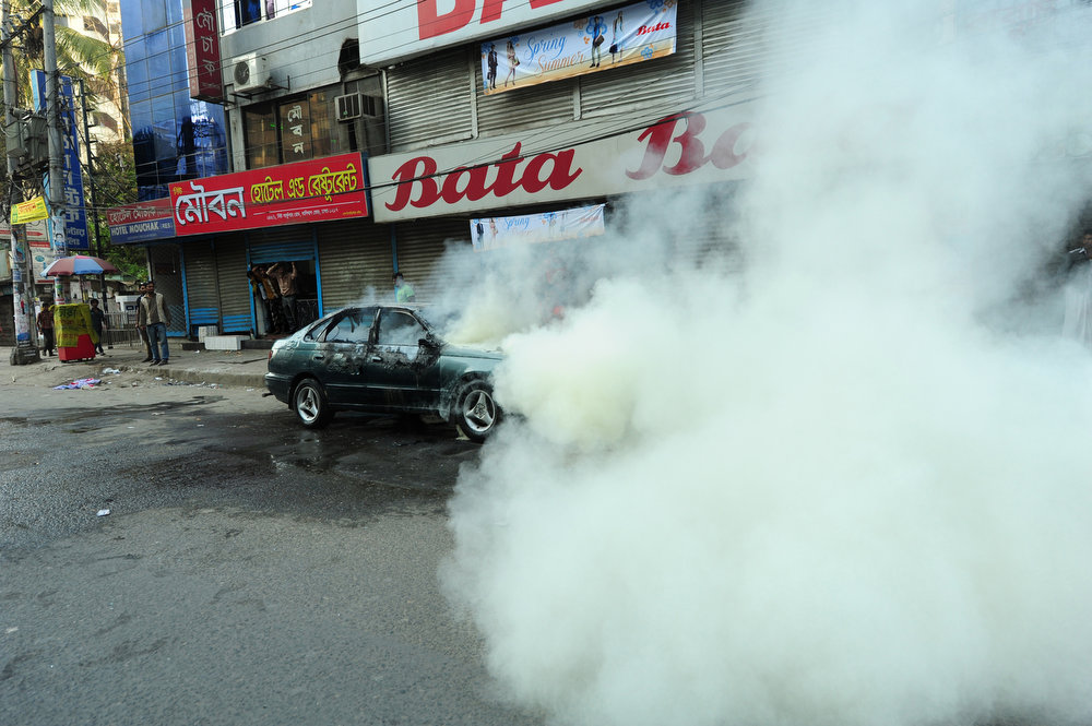 . A car burns during clashes between police and activists on the streets of Dhaka on March 2, 2013.  Activists of the opposition Bangladesh National Party (BNP) and Jamaat-e-Islami party vandalized some vehicles, torched three private cars and blasted a few locally made hand bombs during the clash.   STRINGER/AFP/Getty Images