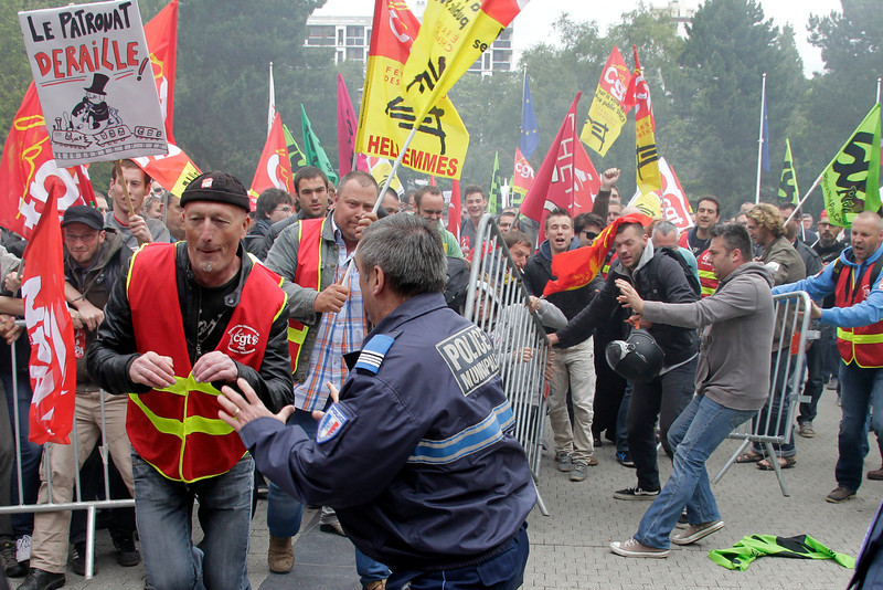 . French rail workers clash against municipal police during a demonstration  in front of the City Hall of Lille, northern France, Tuesday, June 17, 2014.  A weeklong strike by rail workers has caused one of the worst disruptions to the country�s rail network in years _ and is heating up as the reform bill goes to the lower house of Parliament for debate Tuesday. The bill would unite the SNCF train operator with the RFF railway network, which would pave the way to opening up railways to competition. Workers fear the reform will mean job losses and security concerns. The government says the reform is needed to create a stronger structure for the railways, as France and other European countries gear up for full-scale railway liberalization in coming years. (AP Photo/Michel Spingler)
