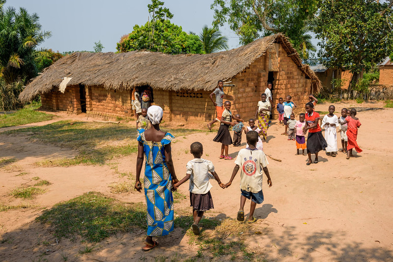 """Grace Mukoma, 10  yr-old boy, walks to church with his mother Mbombo Elize and his sister, Harriet, in Central Kasai Province, Kananga, DRC.  Grace's family go to a church called Le Lumiere, The Light. He says, """"I like to sing. When the pastor finishes preaching we sing.""""   Grace sings us a song: """"God the Almighty, descend down and help us. Without your help we can do nothing. Come down and help us.""""  Church on Sunday is loud and energetic. The room is packed. It's a special day because new members are being inducted into the church.  Towards the end of the service, the pastors circle Grace and say a special blessing.   Background Grace lives with his widowed mom, Mbombo Elize, sister Harriet, 7, and an extended family of relatives, including his widowed grandmother, Kapinga Godelive, 66.  Mbombo has had 4 children, the first when she was 15. 2 died during the time they had to run away because of the war. Now it's just Grace and his sister Harriet, 7.  They live in the Kasai Centrale province in a place called Katoka. It's a rural community. Grace and his family had to run when war broke out in the DRC.  His father was killed. His mother and her 4 children ran about 2 kilometers down the road from his house towards the Lualua River. They hid there for about 3 months. Unfortunately, because of a lack of food and disease, Grace's brother and a sister died. After about 3 months Grace and his family hesitantly made their way back to their house. It had been burnt and was empty. They've struggled ever since.    Here's a look at Grace's life today:  Home Life  """"Early in the morning I sweep the compound. Then I wash and if there is food I eat. Then I join my friends at the CFS."""" """"Sometimes they send me on other errands. If they need something, they send me.""""  Food Grace's family doesn't have enough food. On any given day they may or may not eat. When they do eat, it's once a day, usually in the evening. They often go to bed hungry. At the CFS they have a feeding program. W"""