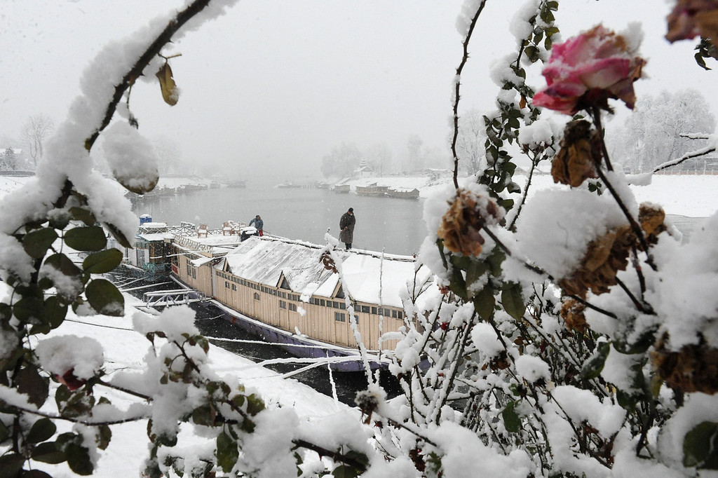 . A Kashmiri clears snow off the roof of a house boat in Srinagar on December 31, 2013. A cold wave further tightened its grip in Jammu and Kashmir with most places in the state recording sub-zero temperatures. ROUF BHAT/AFP/Getty Images