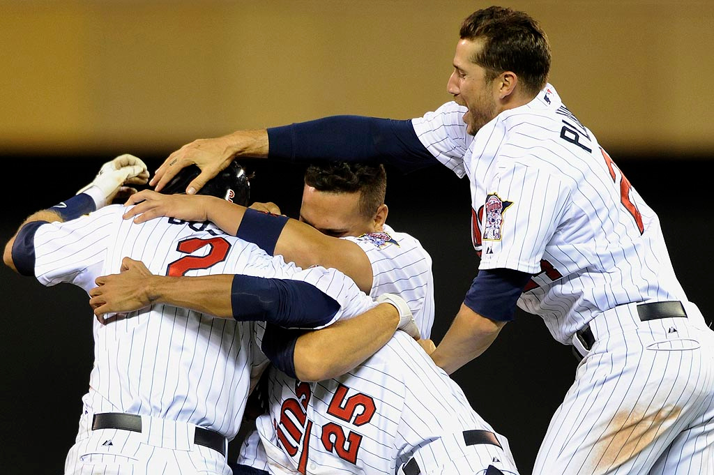 . Brian Dozier #2, Pedro Florimon #25, Oswaldo Arcia #31 and Trevor Plouffe #24 of the Minnesota Twins celebrate a walk off single by Dozier in the13th inning. (Photo by Hannah Foslien/Getty Images)