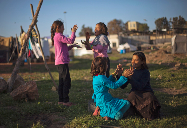 . In this Friday, April 4, 2014 photo, Syrian girls play in an unofficial refugee camp on the outskirts of Amman, Jordan. Some residents, frustrated with Zaatari, the region\'s largest camp for Syrian refugees, set up new, informal camps on open lands, to escape tensions and get closer to possible job opportunities.(AP Photo/Khalil Hamra)