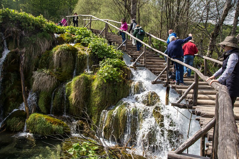hikers climb wooden stairs next to a waterfall in Croatia.