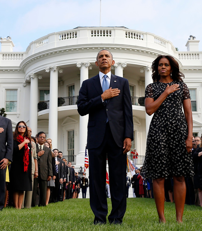 . President Barack Obama and first lady Michelle Obama stand during the playing of Taps on the South Lawn of the White House in Washington, Thursday, Sept. 11, 2014, as they observe a moment of silence to mark the 13th anniversary of the 9/11 attacks. (AP Photo/Charles Dharapak)