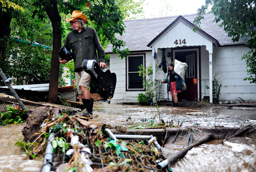 """. Gary McCrumb, left, and Jean Ballhorn wade through flood waters as they carry valuables out of their home, 414 Park Dr., in Lyons Friday, Sept. 13, 2013. McCrumb is planning to stay with friends in town. \""""We\'re all taking care of each other,\"""" said McCrumb. For more photos visit www.TimesCall.com. (Greg Lindstrom/Times-Call)"""