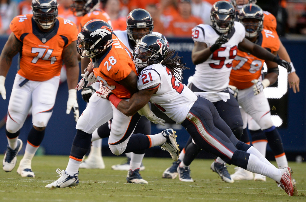 . DENVER, CO - AUGUST 23: Denver Broncos running back Montee Ball (28) is brought down by Houston Texans free safety Kendrick Lewis (21) after a short gain during the first quarter August 23, 2014 at Sports Authority Field at Mile High Stadium. (Photo by John Leyba/The Denver Post)