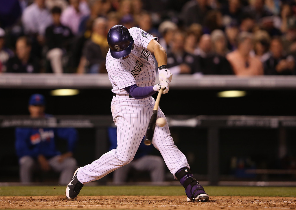 . Nolan Arenado #28 of the Colorado Rockies connects for a single off of Carlos Torres #52 of the New York Mets in the seventh inning at Coors Field on May 2, 2014 in Denver, Colorado. Arenado extended his hit streak to 22 consecutive games.  (Photo by Doug Pensinger/Getty Images)