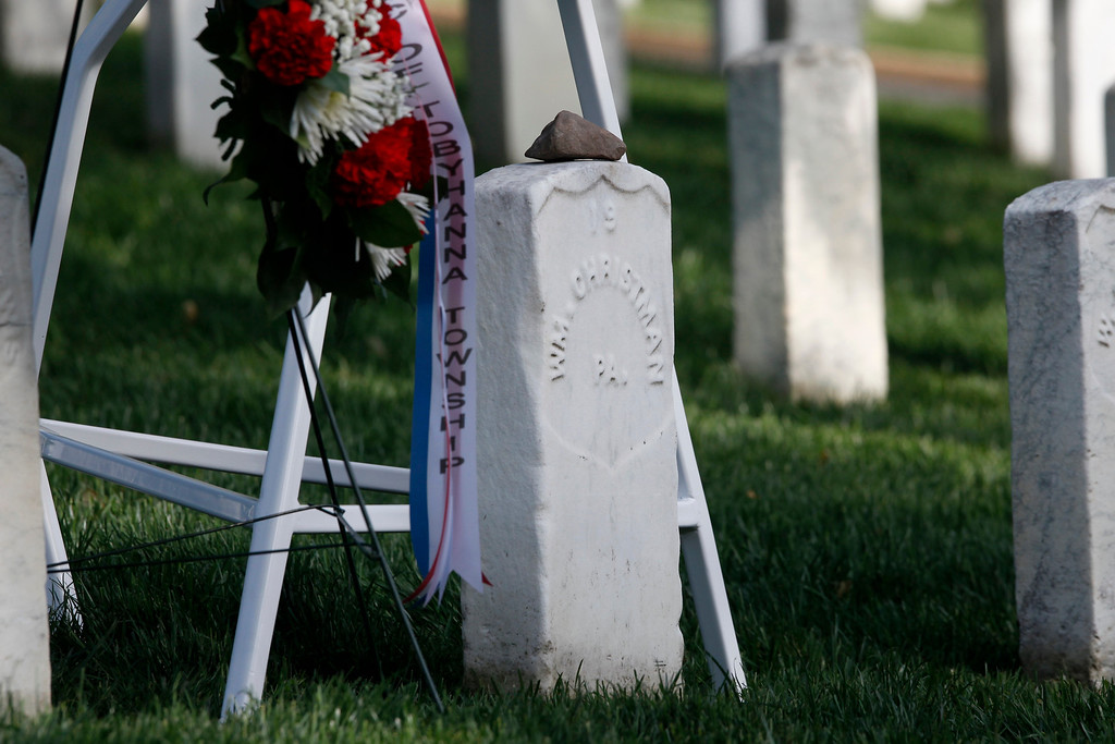 . A stone of remembrance sits on the gravestone of Army Pvt. William Christman, who was the first military burial at the cemetery, marking the beginning of commemorations of the 150th anniversary of Arlington National Cemetery in Arlington, Va., Tuesday, May 13, 2014. The stone is from the original Christman home that still stands in Pocono Lake, Pennsylvania.  (AP Photo)