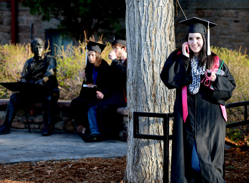 . Lauren Shirley, right, makes a call while Carina Kee and Witt Keller have breakfast near the Robert Frost statue before the 2013 University of Colorado Spring in Boulder Colo. (AP Photo/The Daily Camera, Cliff Grassmick)