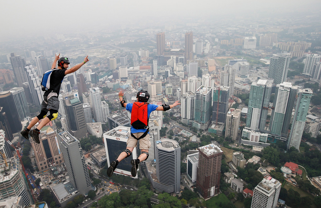 . Base jumper Kieran Olivier Julien Chacornac, right, and Christian Gomis of France leap from the 300-meter Open Deck of the Malaysia\'s landmark Kuala Lumpur Tower during the International Tower Jump in Kuala Lumpur, Friday, Sept. 27, 2013. (AP Photo/Vincent Thian)