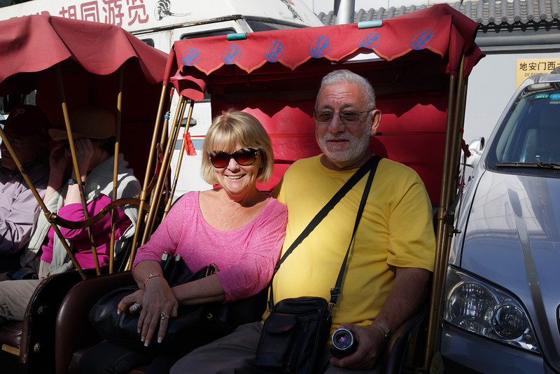"""Mary Sue (""""Susan"""") and Peter Norberto in Beijing.  The rickshaw, the most popular form of transportation in recent years for tourists to take the Hutong tour, provides a unique view of Beijing and is popular with tourists. A rickshaw is more expensive than taking a taxi but allows tourists opportunities to enjoy the street scene and helps to avoid traffic jams. So by taking a rickshaw and traveling at a leisurely pace, one can gain a more intimate flavor of life in old Beijing. Rickshaws can always be found at the important transportation hubs located at the city center and the tourist areas. The legal rickshaw drivers are easily identified by a chest plate carrying their names and the supervision telephone number.  There are thousands of varied hutongs in Beijing, and the most famous hutongs concentrate in the areas around Shicha Lake.  Source: http://www.beijingtrip.com/transport/rickshaw.htm"""