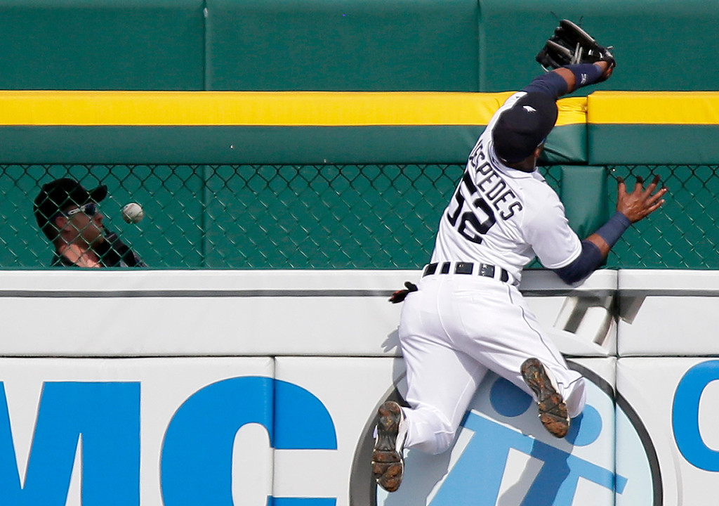 . Detroit Tigers left fielder Yoenis Cespedes knocks the home run ball hit by Cleveland Indians\' Brandon Moss while trying to make a swiping catch during the ninth inning of a baseball game Sunday, June 14, 2015, in Detroit. The Tigers defeated the Indians 8-1. (AP Photo/Duane Burleson)