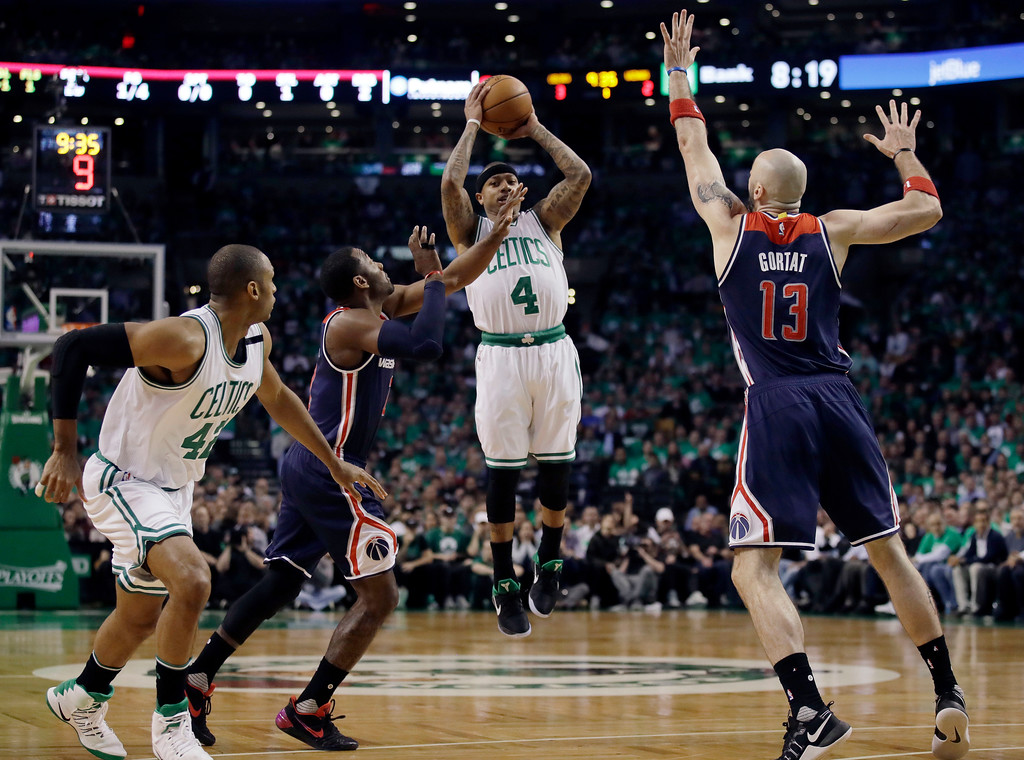 . Boston Celtics guard Isaiah Thomas (4) shoots between Washington Wizards guard John Wall, left, and Wizards center Marcin Gortat (13) during the first quarter of Game 7 of a second-round NBA basketball playoff series, Monday, May 15, 2017, in Boston. (AP Photo/Charles Krupa)
