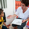 Volunteer helps a boy learn English.