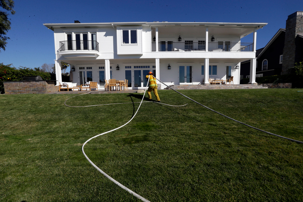 . A Los Angeles firefightrer pulls hose from a Blufftop mansion Wednesday, Jan. 15, 2014, after a fire threatened bluff top homes Tuesday afternoon in Los Angles.  As Santa Ana winds made moisture plunge, plant life wither and wildfire danger soar, Southern California firefighters pounced on several small blazes before they could surge, though another day of dryness awaited. (AP Photo/Reed Saxon)