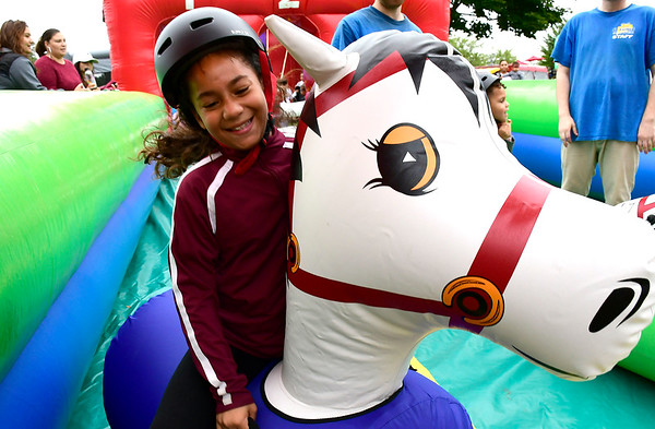 9/8/2018 Mike Orazzi | Staff Letty Rodriguez rides an inflatable horse during Main Street USA held in New Britain's Walnut Hill Park Saturday.