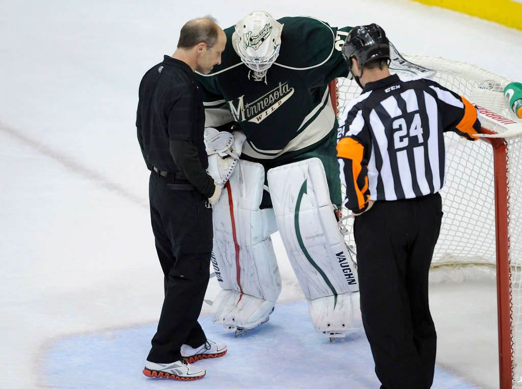 . Wild goalie Josh Harding is checked on by a trainer after a collision with Chicago\'s Jonathan Toews during the first period. (Photo by Hannah Foslien/Getty Images)