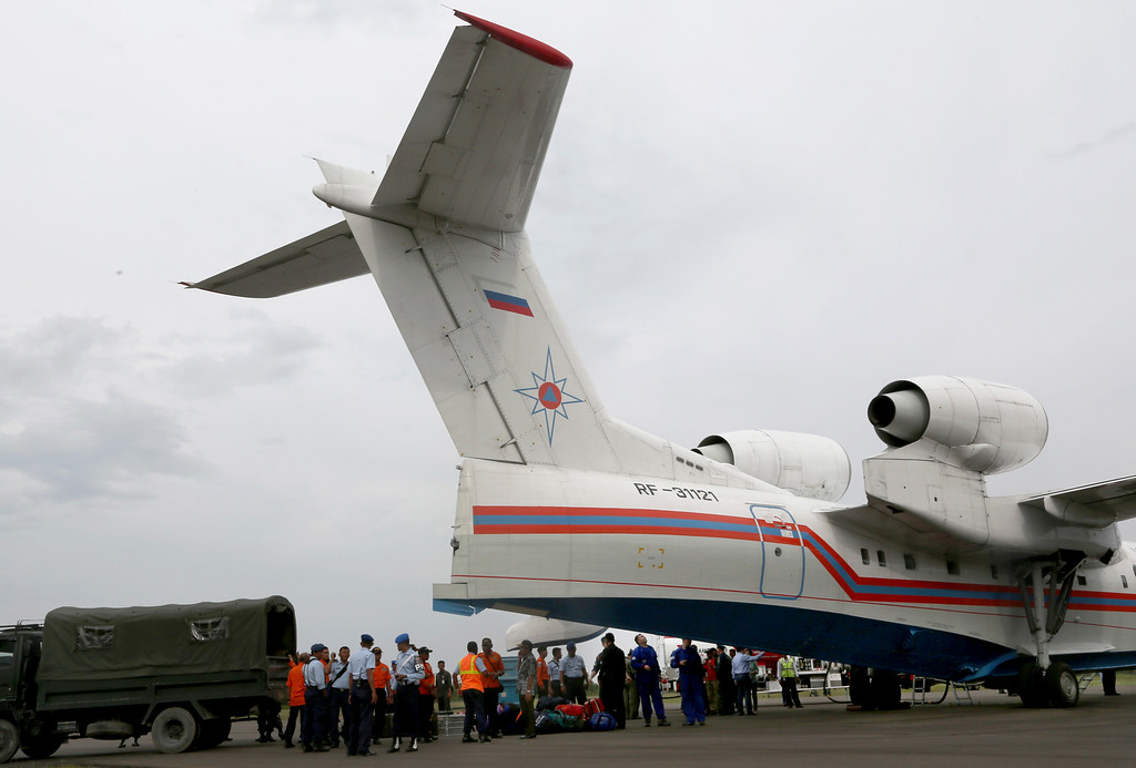 . Russian rescuers unload gear from their Beriev Be-200 amphibious aircraft upon arrival to reinforce a search operation for the victims and the wreckage of the ill-fated AirAsia Flight 8501 at Pangkalan Bun Airport, Indonesia, Saturday, Jan. 3, 2015. Indonesian officials were hopeful Saturday they were honing in on the wreckage of the plane after sonar equipment detected two large objects on the ocean floor, a full week after the plane went down in stormy weather. (AP Photo/Tatan Syuflana)