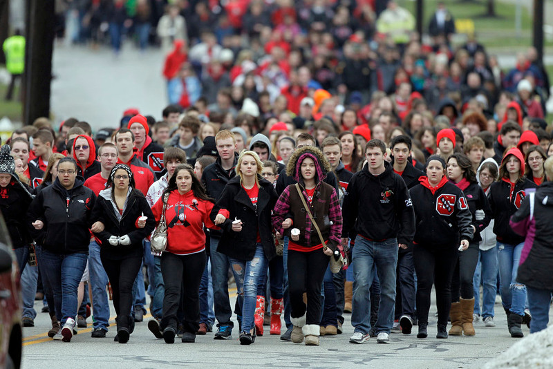. Chardon High School students march to the square in Chardon, Ohio for a memorial ceremony for three classmates who died in a school shooting rampage one year ago, Wednesday, Feb. 27, 2013. The march ended at the courthouse where 18-year-old shooter T.J. Lane pleaded guilty to all charges. (AP Photo/Mark Duncan)