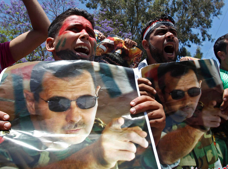 . Syrians carry pictures of Syria\'s President Bashar al-Assad and shout slogans during a protest in support of Syria\'s regime, in Sidon, southern Lebanon, May 12, 2013. REUTERS/Ali Hashisho