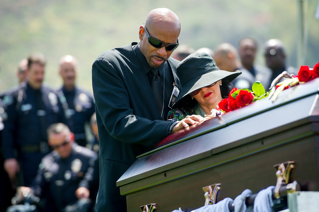 . Dan Holbert  stands with Lillie Price at the casket of LAPD officer Chris Cortijo, Tuesday, April 22, 2014, at Forest Lawn Hollywood Hills. (Photo by Michael Owen Baker/L.A. Daily News)