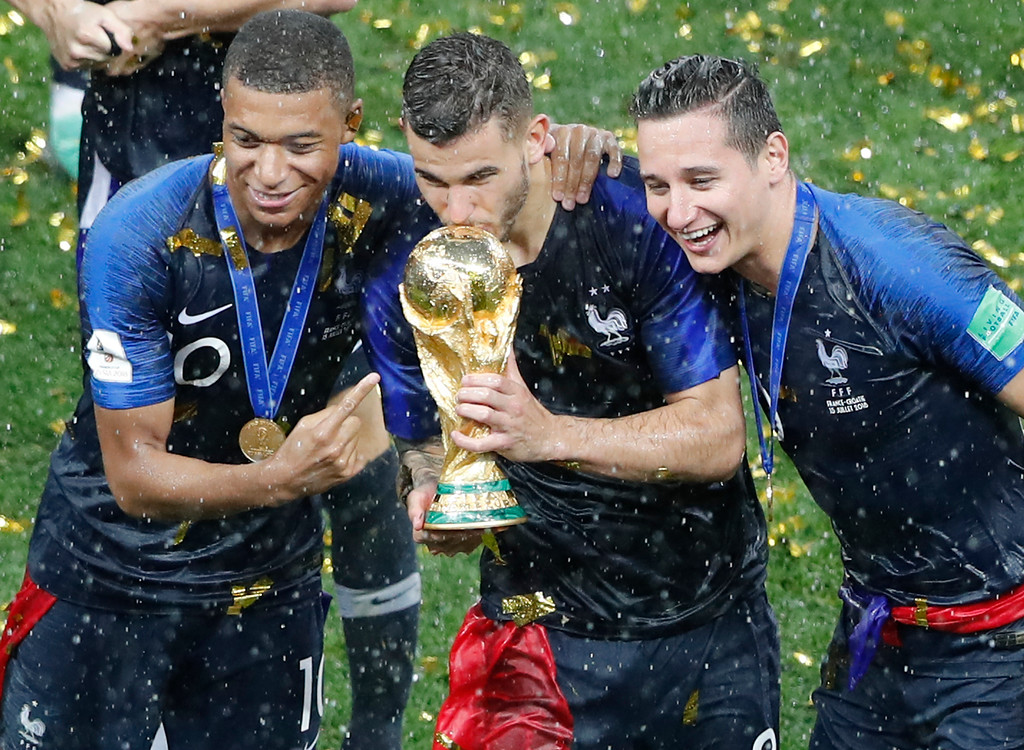 . France\'s Kylian Mbappe, Lucas Hernandez, Florian Thauvin hold the trophy after the final match between France and Croatia at the 2018 soccer World Cup in the Luzhniki Stadium in Moscow, Russia, Sunday, July 15, 2018. (AP Photo/Frank Augstein)