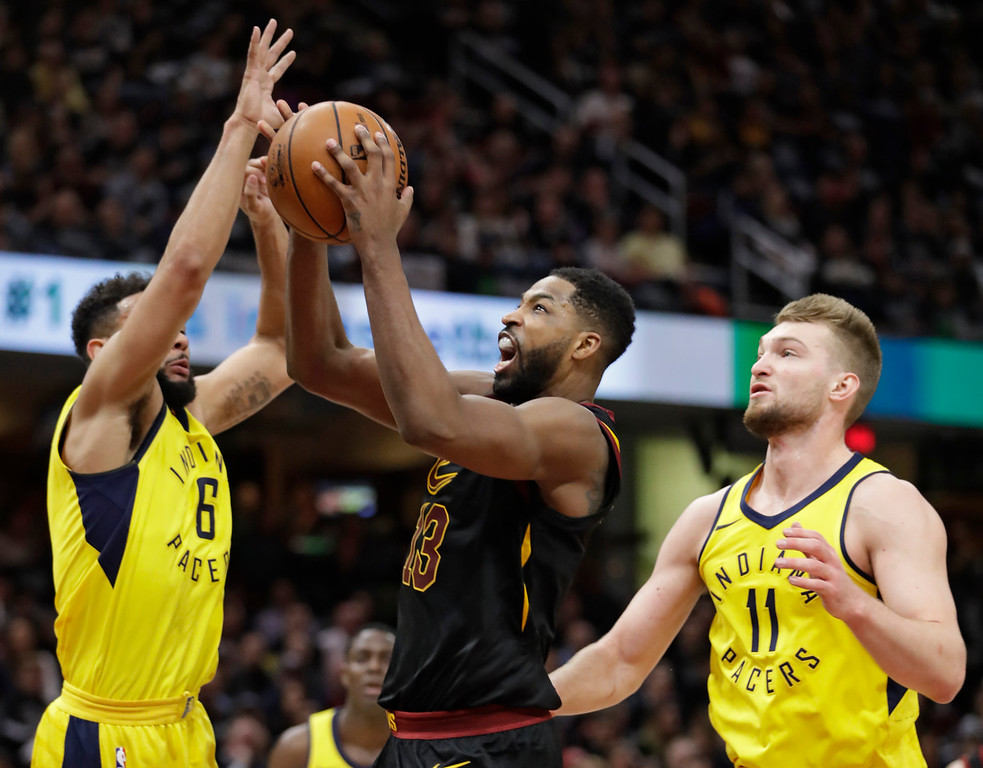 . Cleveland Cavaliers\' Tristan Thompson, center, shoots between Indiana Pacers\' Cory Joseph, left, and Domantas Sabonis, from Lithuania, in the first half of Game 7 of an NBA basketball first-round playoff series, Sunday, April 29, 2018, in Cleveland. (AP Photo/Tony Dejak)