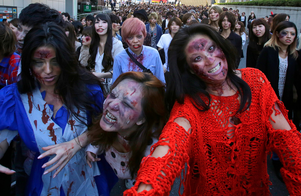 . Participants wearing zombie makeup, perform during a Halloween event at Tokyo Tower in Tokyo, Thursday, Oct. 31, 2013. (AP Photo/Shizuo Kambayashi)
