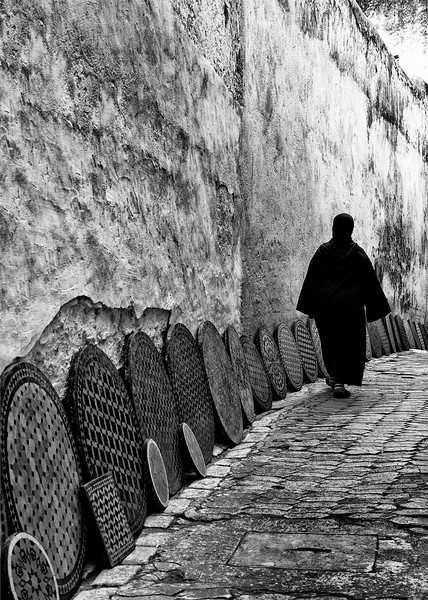 Woman walking past a display of traditional Moroccan tables. 