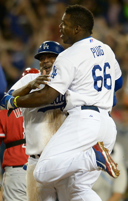 . Juan Uribe and Yasiel Puig celebrate after reaching home on a walk off single by Andre Ethier in the 9th inning. The Dodgers defeated the Angels 5-4. Los Angeles, CA. 8/5/2014(Photo by John McCoy Daily News)