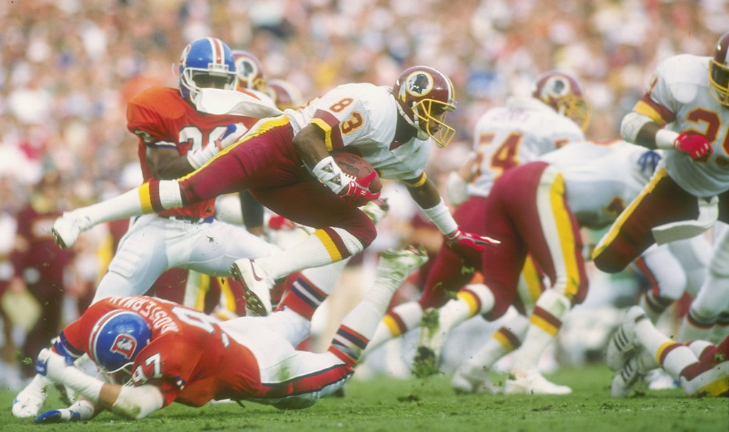 . Wide receiver Ricky Sanders of the Washington Redskins #83 leaps over a diving defensive player of the Denver Broncos during Super Bowl XXII at Jack Murphy Stadium in San Diego, California.  Rick Stewart/Allsport
