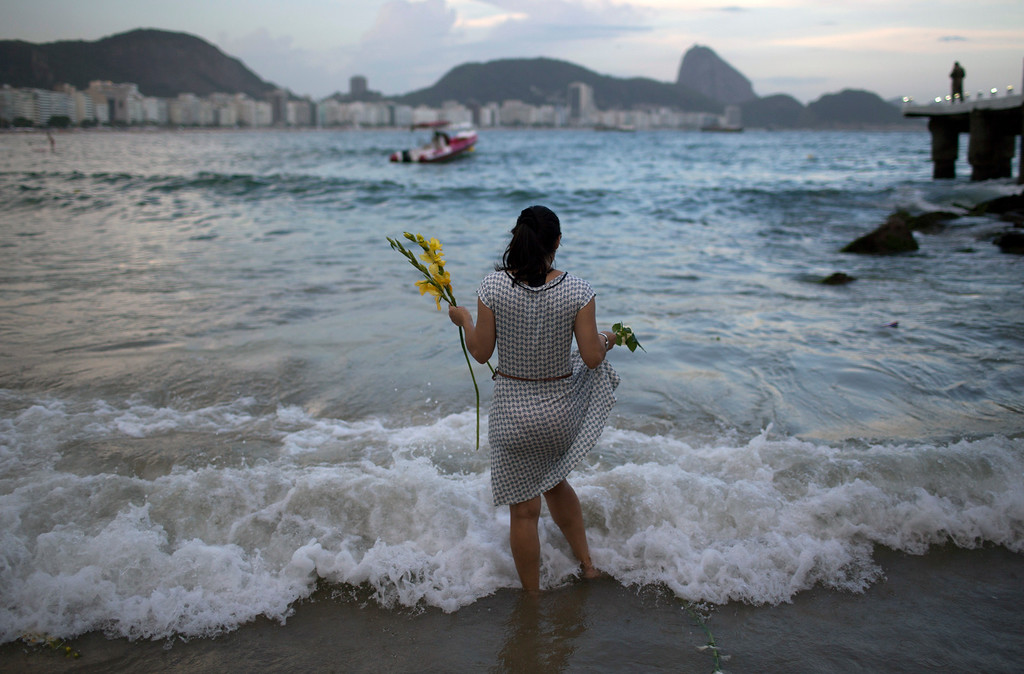 . A woman offers flowers to Yemanja, goddess of the sea, for good luck in the coming year during New Year\'s Eve festivities on Copacabana beach in Rio de Janeiro, Brazil, Saturday, Dec. 31, 2016. The belief in the goddess comes from the African Yoruba religion brought to America by West African slaves. (AP Photo/Leo Correa)