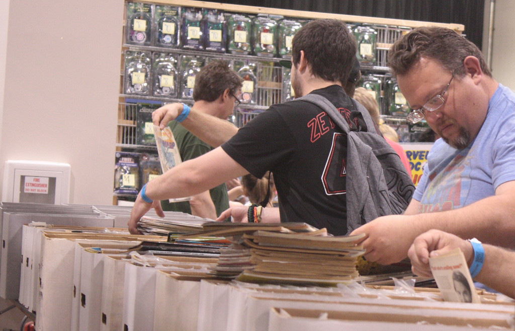 . Fans search for elusive titles in the comic bins. (Photo by Erica McClain)