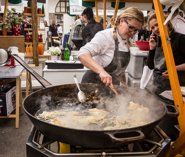 Woman cooking in a giant frying pan at a Slovenia outdoor food festival.